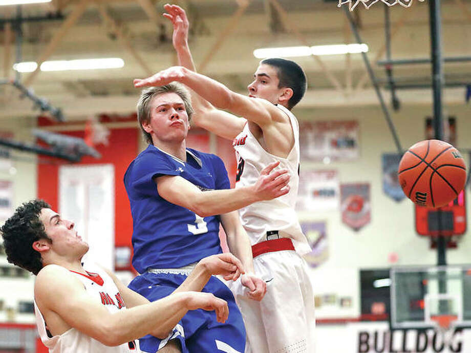 Marquette's Sammy Green, middle, gets off a no-look pass against the defense of Highland's Sam LaPorta, left, and Steven Torre during Tuesday night's game in Highland. The Explorers win 48-37 and push their record to 25-0. Photo: Billy Hurst | For The Telegraph
