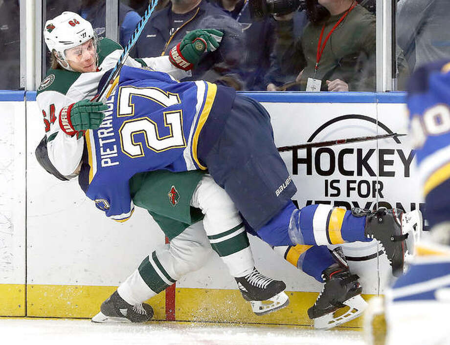 Mikael Granlund of Minnesota, left, is checked into the boards by the Blues' Alex Pietrangelo during Tuesday night's game in St. Louis. Photo: Jeff Roberson | AP Photo