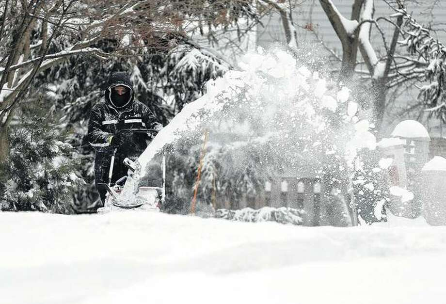 A man clears snow from sidewalk Friday in Wheeling as a winter storm makes its way through Illinois.