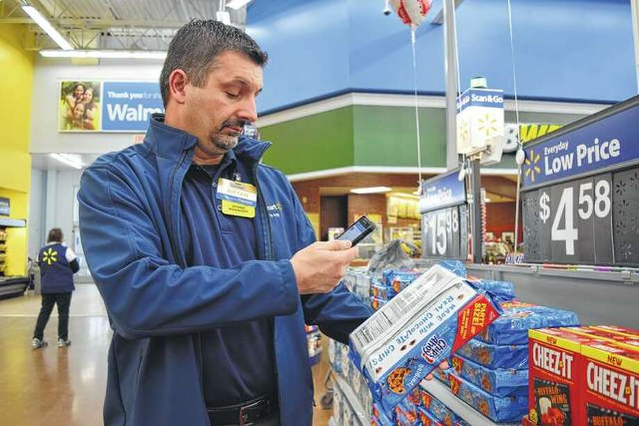 Jacksonville Walmart store manager Bryan Neeley scans cookies with his phone to demonstrate the new Scan & Go app.