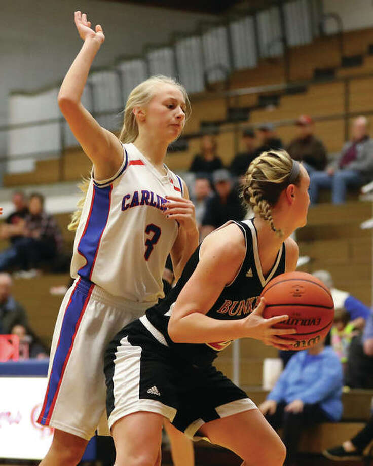 Carlinville's Rachel Olroyd (left), shown defending while Bunker Hill's Brooke Morell looks for a teammate in a Dec. 18 game in Carlinvile, scored 18 points Wednesday night to lead the Cavaliers to a double-overtime victory over Gillespie in the semifinals of the Litchfield Class 2A Regional. Photo: Billy Hurst / For The Telegraph