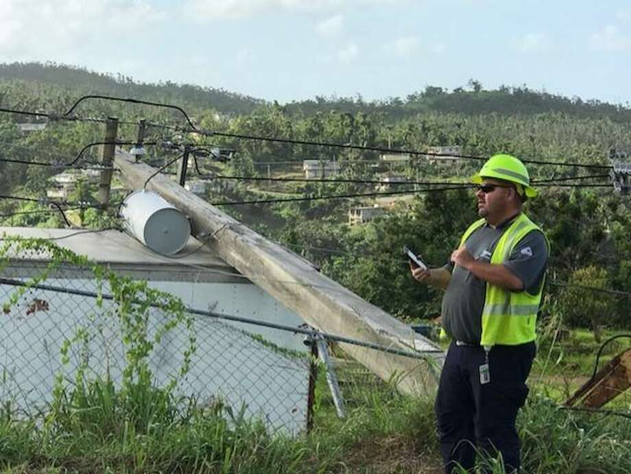 Brian Doran, an Ameren Illinois supervisor who worked in Alton for four years, surveys a downed power pole that landed on a building in Rio Grande, Puerto Rico, during Hurricane Maria in September. Doran, of the Worden area, is a member of a crew that is restoring the island's electric infrastructure and power to residents. Many people in Puerto Rico have been without power for nearly five months. Photo: For The Telegraph