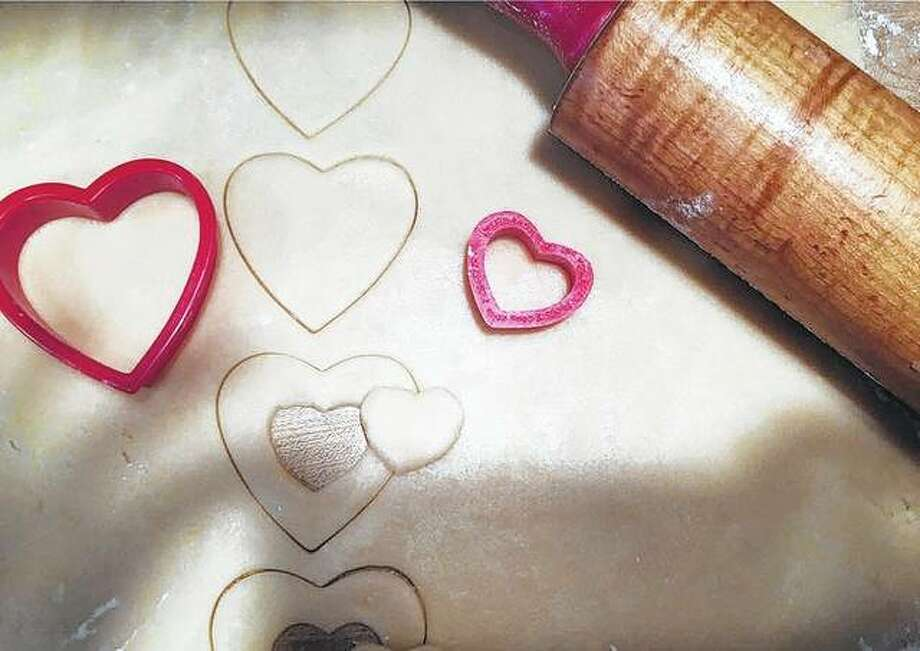 A baker makes homemade heart-shaped cookies for Valentine's Day.
