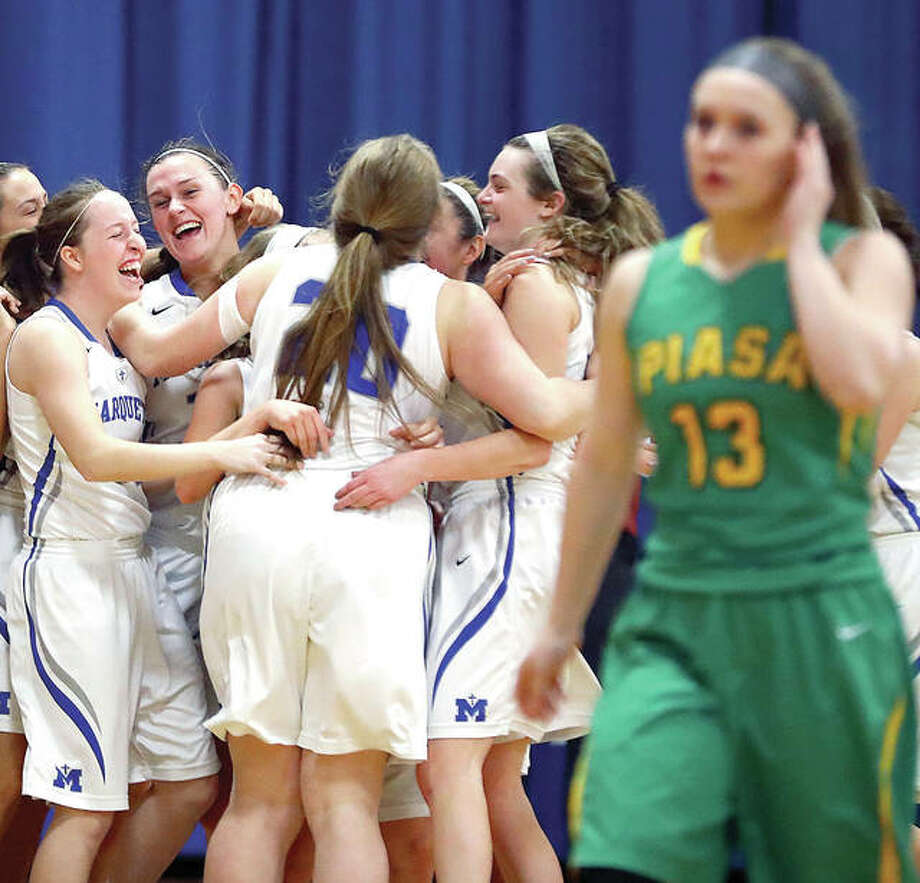 Members of the Marquette Explorers celebrate as Southwestern's Natalie Keith, right, heads for the locker room at the conclusion of Thursday night's Marquette 2A Regional championship gamein Alton. The Explorers defeat the Piasa Birds 34-24. Photo: Billy Hurst | For The Telegraph