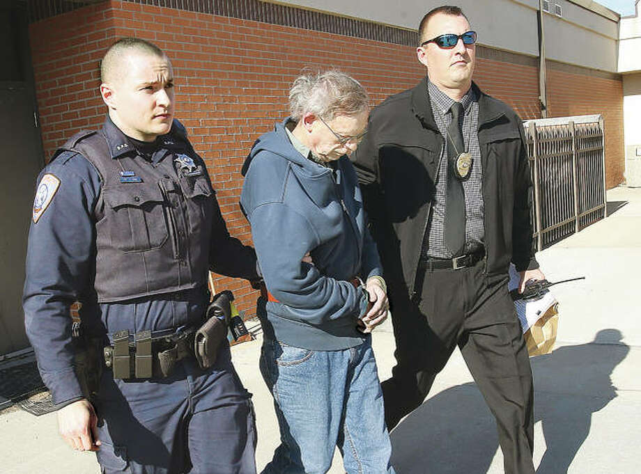 In this photo from last February, Bethalto police officer Jordan Lind, left, and Det. Sgt. Jason Lamb, right, escort David L. Von Bergen to a police car for transfer from Bethalto to the Madison County Jail. Von Bergen was sentenced Friday to 15 years in prison for using hidden cameras to record people in the bathroom of Bethalto's Zion Lutheran Church. Photo: John Badman | The Telegraph