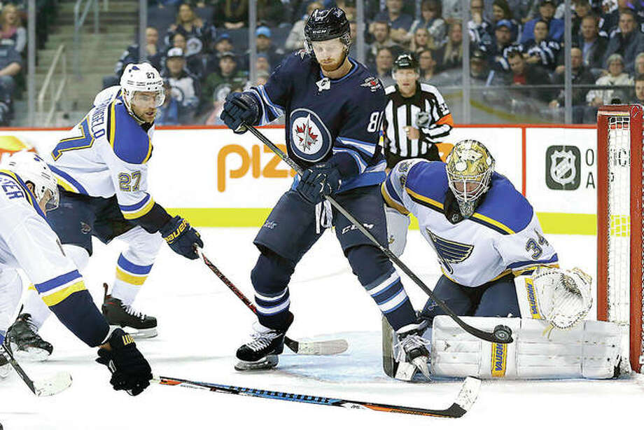 Winnipeg's Kyle Connor (81) attempts to tip the puck past Blues goaltender Jake Allen (34) as Alex Pietrangelo (27) defends during the second period Friday night's game in Winnipeg, Manitoba. Photo: AP