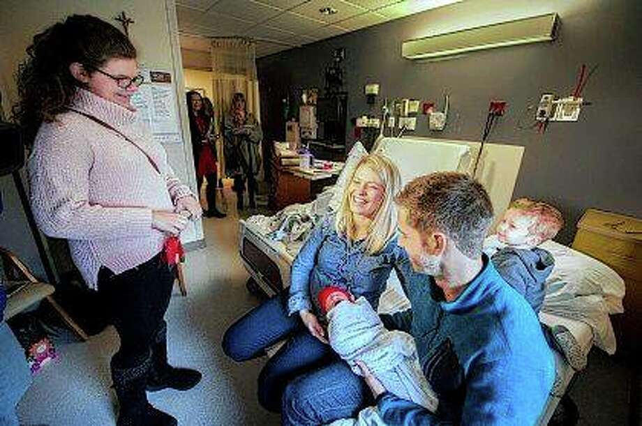 Zaia Wilcoxon (left) visits Dan and Tara Ballard, holding their 1-day-old daughter Nora, with their son, Charlie, in Peoria. Wilcoxon gave parents tiny knitted red hats as part of the American Heart Association event Little Hats, Big Hearts to recognize moms and babies, encouraging them to live heart healthy lives. Wilcoxon herself was born with a heart condition that wasn't discovered until she was 2. Fred Zwicky | Journal Star (AP)