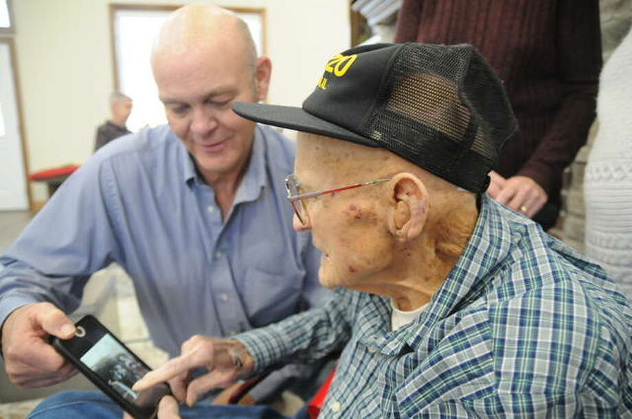 Clyde Miller points to a photo of him and his three brothers, all of whom served in the U.S. Navy in World War II, while his nephew Dennis Hammond looks on. Photo: David Blanchette | For The Telegraph