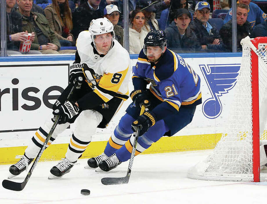 The Penguins' Brian Dumoulin (left) handles the puck as he is pressured by the Blues' Patrik Berglund during the second period Sunday in St. Louis. The Pens scored three goals in the third period to break a 1-1 tie and win 4-1. Photo: Billy Hurst / Associated Press