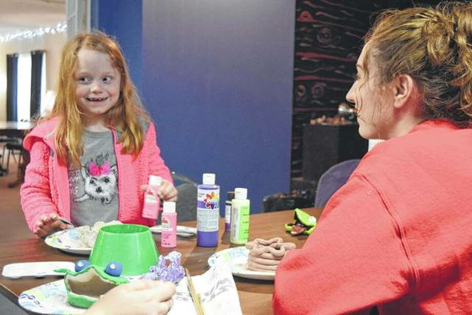 MacMurray College student Nicole Maul helps Kelly Turner, 7, of Jacksonville with a pottery project Monday. Photo: Nick Draper | Journal-Courier