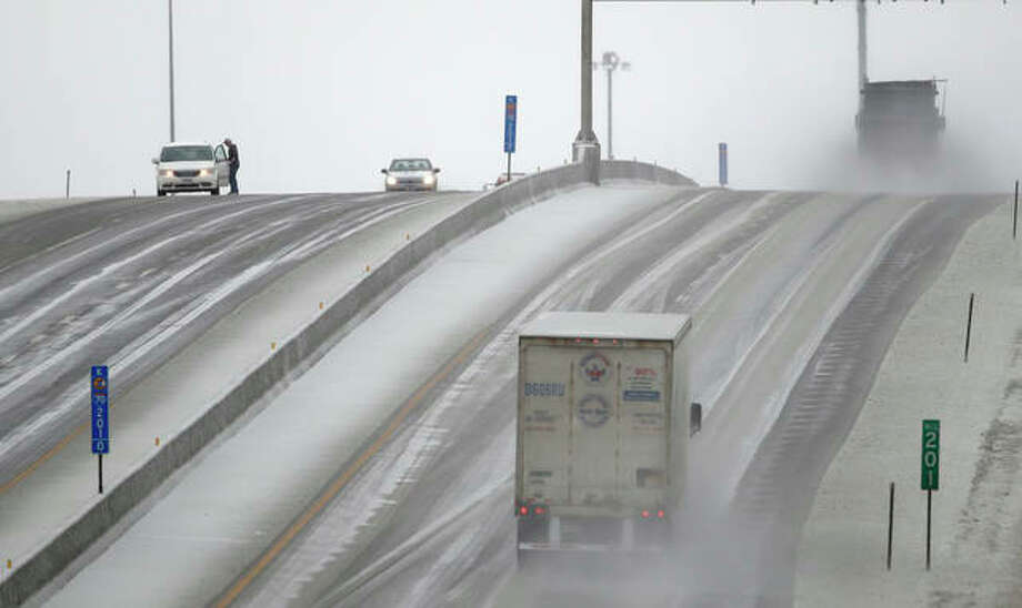 A motorist stops to clear ice from his wipers Tuesday along Interstate 70 near Lawrence, Kansas. The area is under a winter weather advisory. Orlin Wagner | AP