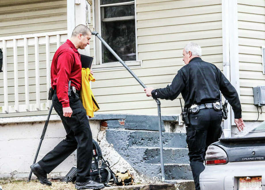 An investigator with the Illinois State Fire Marshal's office follows and Alton police officer into 2309 Amelia St. Saturday afternoon, where 45-year-old Alton man Terry L. Wilson was found dead after firefighters responded to a small fire. The fire was one of two in Alton over the weekend. Photo: Nathan Woodside | For The Telegraph