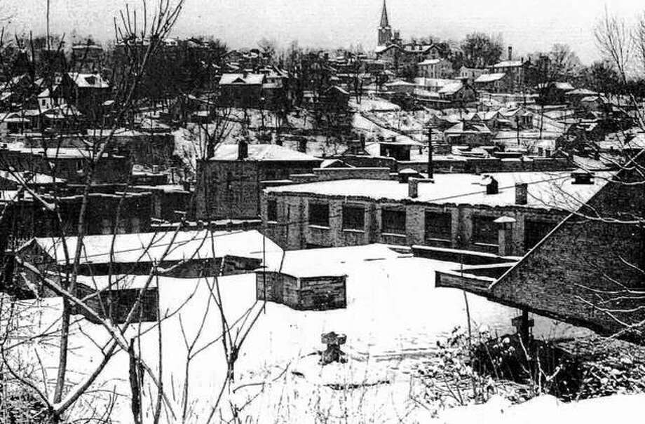 This photo was taken at the intersection of Fourth and Market streets looking west. The rooftops of the manufacturing district can be seen in the foreground and the rooftops covered with snow. The Old Cathedral dominates the skyline, as it has done since it was built. Photo: File Photo