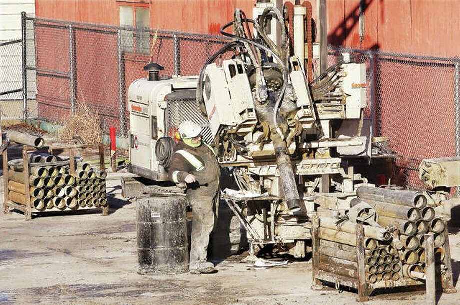 A worker sets up a drilling rig on the former Downtown Alton post office site on Belle Street. Ameren, the owner of the property, is installing cylinders as part of a thermal remediation system that will heat the soil to extract the contaminants which lie under the property. Photo: John Badman   The Telegraph