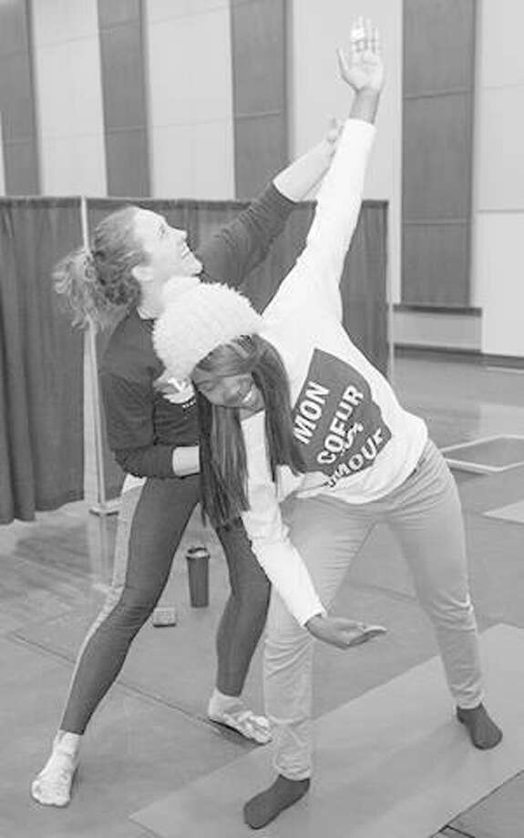 Meredith Banner, a certified yoga instructor, helps Nea Sails, a senior majoring in public health, with some yoga moves. Photo: For The Telegraph