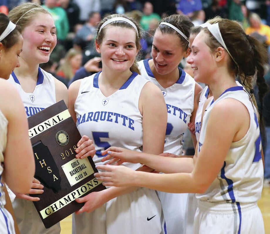 Marquette Catholic's Lila Snider (5) and Regina Guehlstorf (left) hold the championship plaque while Lauren Fischer (back) and Peyton Kline (right) join in the celebration after winning last Thursday's Marquette Class 2A Regional title game in Alton. Photo: Billy Hurst / For The Telegraph