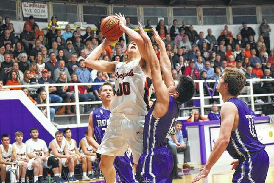 New Berlin's Max Day (00) goes for a shot under the basket at Routt Friday during the championship game of the Routt Regional.