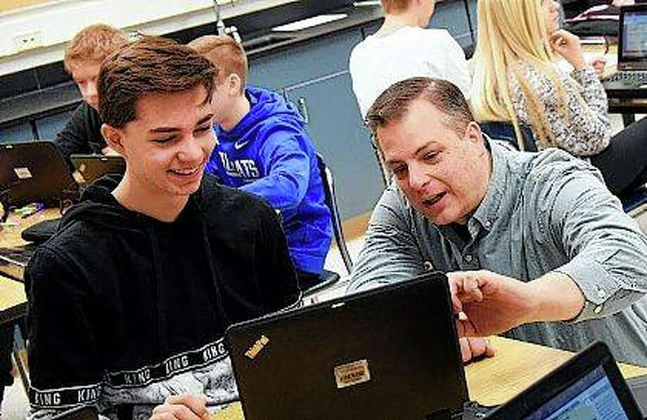 Teacher Matt Gain works with eight-grader Giancarlo Rella during class at Geneva Middle School South. Gain has taught chemistry and physics at the school for 17 years. Rick West | Daily Herald (AP)