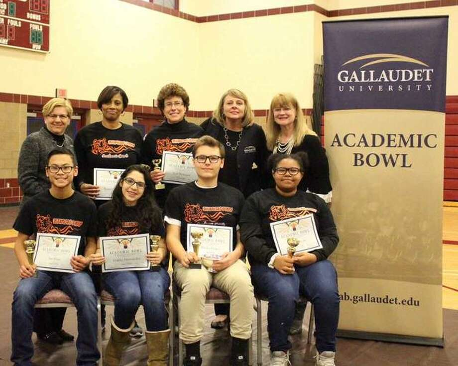 Teammates Ian Fraas (front row, from left), Dahlia Hernandez, Michael Lapa and Olivia Scott and Gallaudet University President Bobbi Cordano (back row, from left), Illinois School for the Deaf coaches Raquel Humphrey and Lori Niemann, Gallaudet University Midwest Regional Ccenter director Sherry Cook and ISD Superintendent Julee Nist show some of the recognition ISD members received in competition.