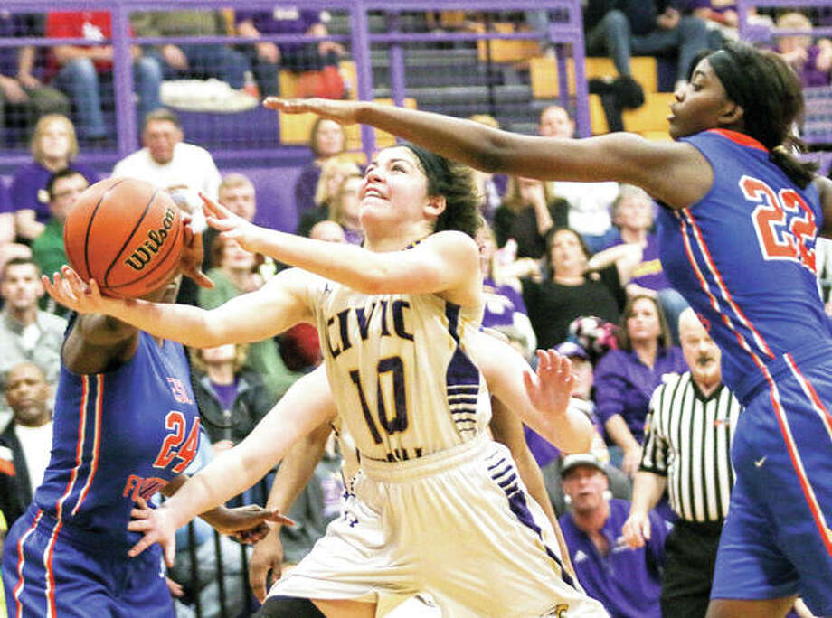 Kourtland Tyus of CM (10) drives against Shawnta Johnson (22) and Kaysie Newson (24) of East St. Louis during Thursday night's championship game of the CM Class 3A Regional Tournament in Bethalto. Photo: Nathan Woodside | For The Telegraph
