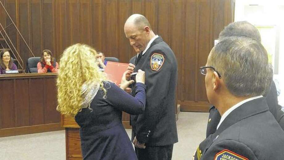 Karen Hopper pins her husband Mike Hopper who was promoted to lieutenant from the Jacksonville Fire Department Monday at the Jacksonville City Council meeting Photo: Nick Draper | Journal-Courier