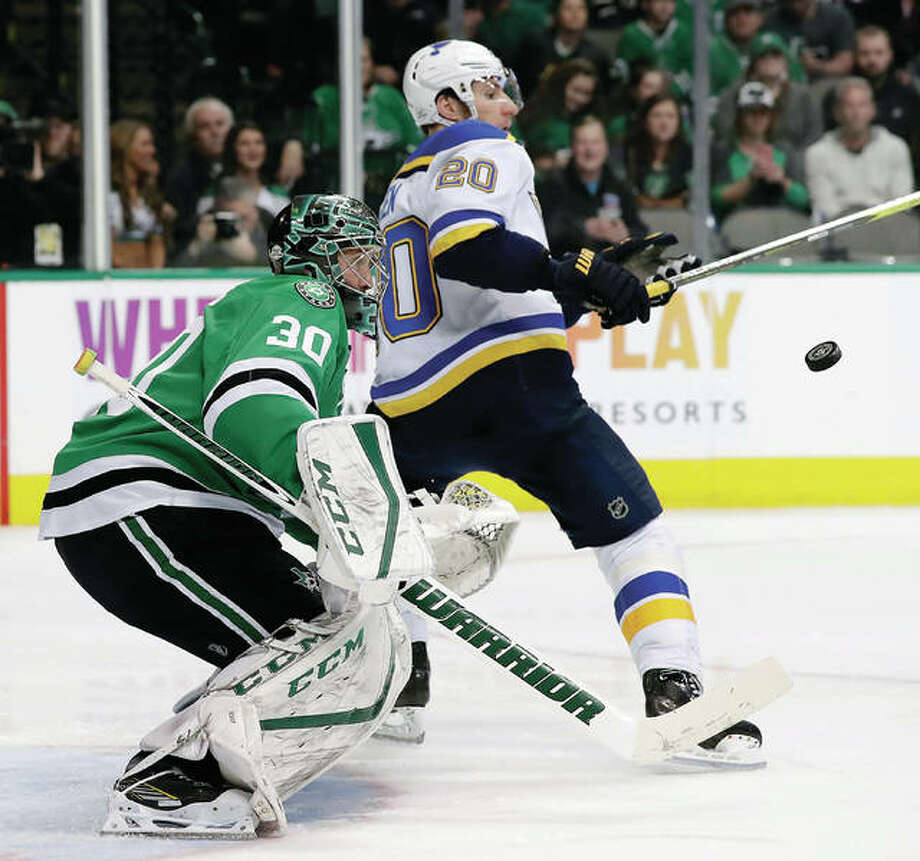 Dallas Stars goalie Ben Bishop (30) defends against an airborne puck in front of the net under pressure from the Blues' Alexander Steen (20) Friday in Dallas.
