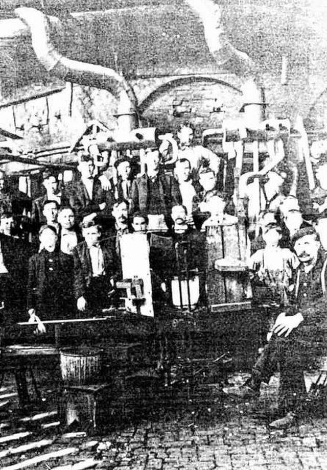 Glassblowers and their helpers (mostly children from the ages of 10 to 16) are shown in front of the early one-furnace operation. The glassblowing process required soda ash, sand, salt and lime. The materials were melted then blown into glass by the craftsman. Boys carried the molten glass to the blowers, then placed the bottles in the furnaces. Boys and girls also comprised the work force that made wicker coverings for many bottles. In 1878, twenty-two boys struck for higher wages. Photo: File Photo