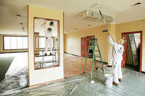 Paul Lariviere, right, and Kevan Zini, left, both from Painting Outfitters in Alton, work on painting the interior of the Woodlands Golf Course clubhouse Friday. Woodlands Golf Club owners Joe Boston and Brian Curry purchased the 160-acre property last April and, most recently, the club is in the last phases of extensive remodeling and renovation, including to its clubhouse, which has a full-service bar; extension of its outdoor patio; and, a kitchen addition. Big Boy's Q & Southern Soul at The Woodlands also will open adjacent and contiguous to the clubhouse Tuesday, March 27. The golf club was last remodeled in 1999.
