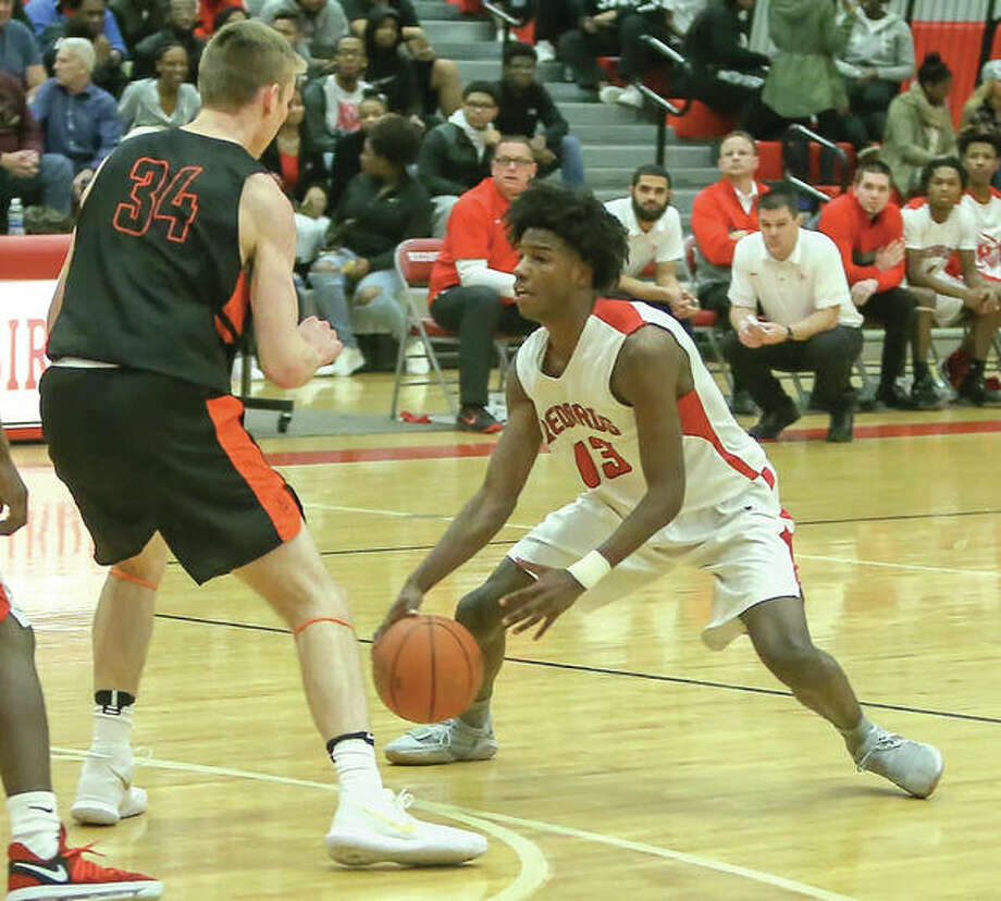 Alton's Malik Smith (right) handles the ball outside the arc while Edwardsville's Caleb Strohmeier defends during the Tigers' Southwestern Conference boys basketball victory Friday night at Alton High in Godfrey. The Redbirds completed their lost weekend Saturday night at AHS with a defeat to Taylorville. Photo: Scott Kane / For The Telegraph