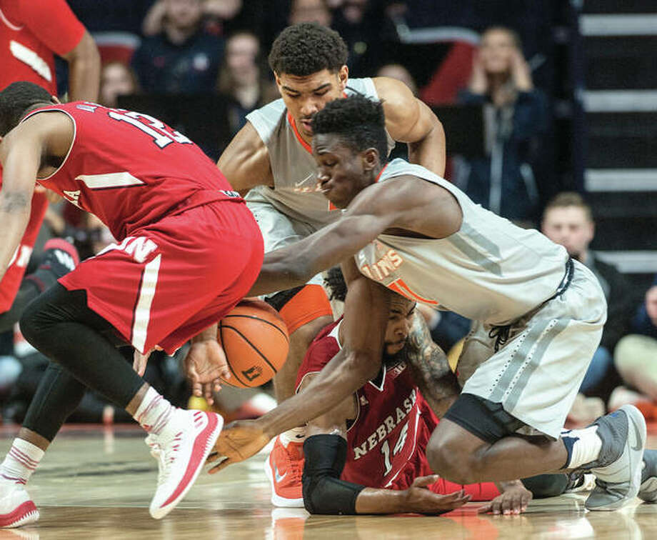 Illinois' Greg Eboigbodin (front right) and Mark Smith (back) battle for a loose ball with Nebraska's Thomas Allen (left) Isaac Copeland (bottom) during the second half Sunday afternoon in Champaign. Photo: Associated Press