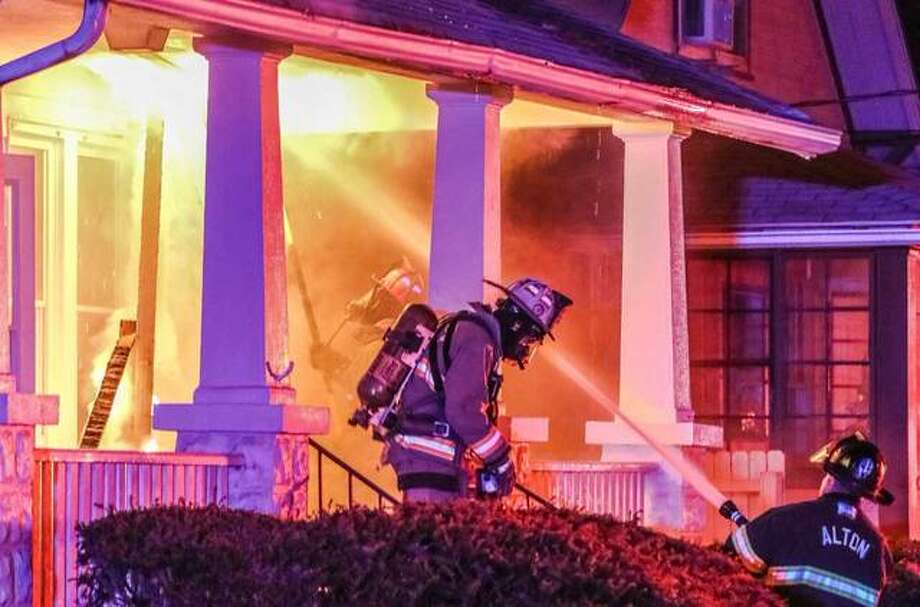 Firefighters avoid a rush of flames — as oxygen hit the flames — escaping from the roof of the front porch during a blaze that destroyed a home at 1126 Central Avenue in Alton. The call came at approximately 7:15 p.m. A witness on the scene said they were passing by when they noticed flames coming from the second floor of the home, and called 911. The home's occupant didn't appear to be home at the time, and there were no apparent injuries, however official reports were not available as of Sunday evening. Godfrey firefighters assisted Alton crews. Personnel remained on scene for several hours. Radio traffic indicated the fire was most intense in the attic area of the house, and with little oxygen, making it a possibly-dangerous scenario for firefighters. Photo: Photos By Nathan Woodside | For The Telegraph