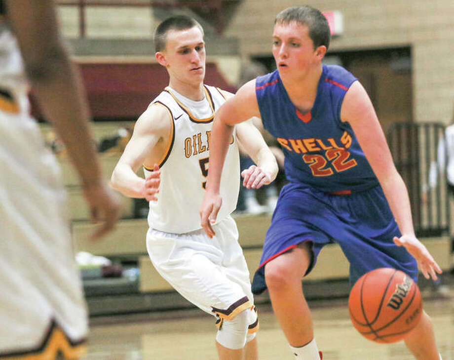 Roxana's Jacob Golenor (right) heads toward the basket after driving past East Alton-Wood River's Justin Englar during the Shells' semifinal victory Monday night in the EA-WR Class 2A Regional at Memorial Gym in Wood River. Photo: Nathan Woodside / For The Telegraph