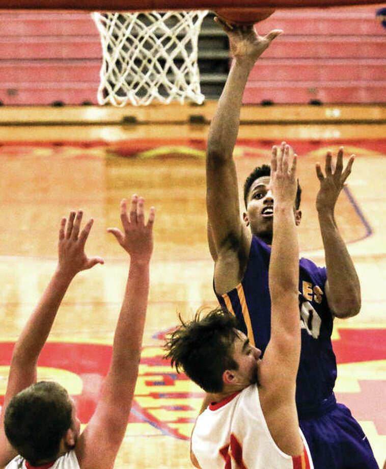 Civic Memorial's Jaquan Adams (back) shoots over Roxana's Eddie Lara (11) during an Eagles win Dec. 15 in Roxana. On Tuesday night in an overtime loss at Highland, Adams scored 25 points to rise to No. 4 on CM's all-time scoring chart Photo: Nathan Woodside / For The Telegraph