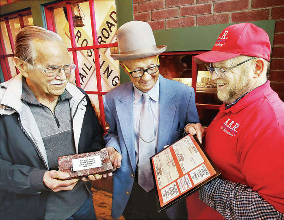 John Langley, center, secretary of the board of directors for the Alton Museum of History and Art, accepts a gift to the museum Thursday of a brick from the recently razed Amtrak station in Alton and the last ticket sold at the station, framed with the first ticket sold at the new Amtrak station. Frank Altman, left, of Arnold, Missouri, and Rich Eichhorst, president of the American Association of Railroaders Inc., right, donated the items to be added to the museum's collection of Alton train history. Photo: John Badman | The Telegraph