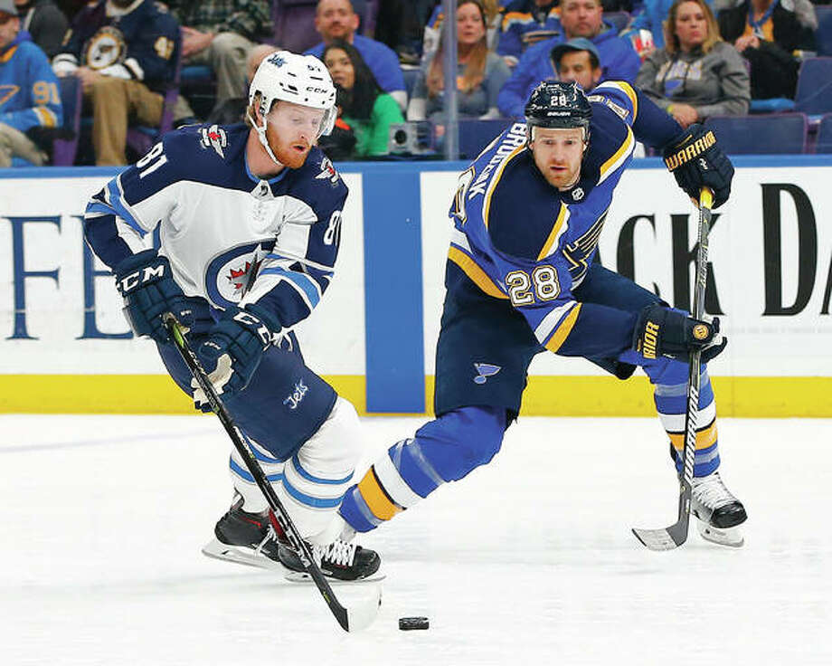 Winnipeg's Kyle Connor, left, handles the puck as he is pressured by the Blues' Kyle Brodziak Frida night in St. Louis. Photo: AP