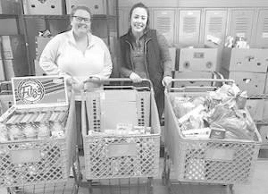 Grocery carts of food were the result of a friendly competition between Kappa Delta Pi (KDP) International Honor Society in Education and the Delta Sigma Pi, Professional Business Fraternity. Pictured are Sierra Hyman, KDP co-president, left, and Makenzi Fee, Community Service vice president of Delta Sigma Pi, with the grocery carts. Photo: For The Telegraph