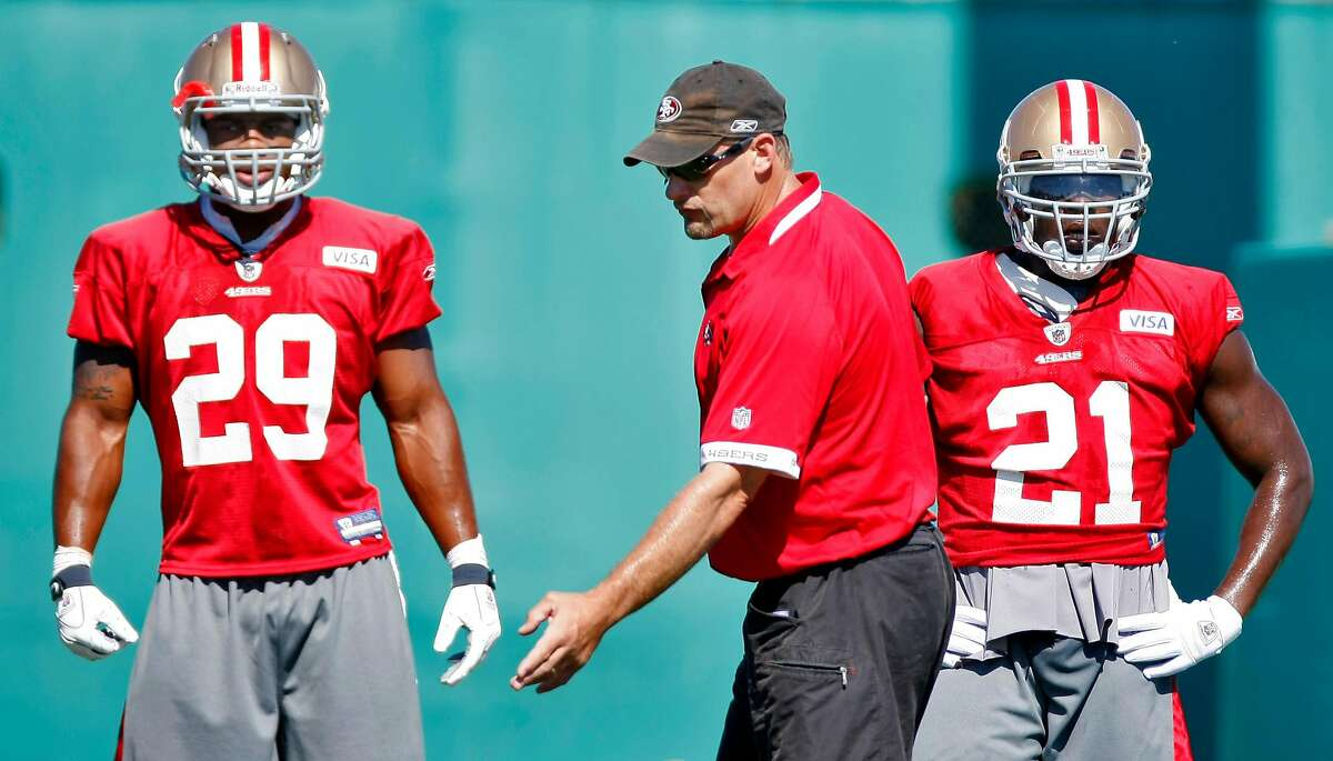 San Francisco 49ers running back coach Tom Rathman, center talks with Glen Coffee, left and Frank Gore during practice, Sunday Aug. 1, 2010, in Santa Clara, Calif.