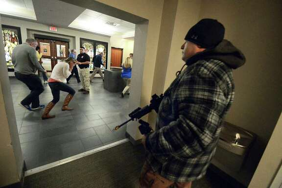 Lackawanna County Sheriff Cpl. Glenn Capman portrays an armed gunman as Lackawanna County workers run for cover on Wednesday, Feb. 21, 2018, at Marywood University in Scranton, Pa., during an active shooter training program. Cpl. Capman created and wrote an active shooter policy for Lackawanna County, Pennsylvania. He is carrying a real AR-15 rifle which was firing blanks. (Butch Comegys/The Times & Tribune via AP)