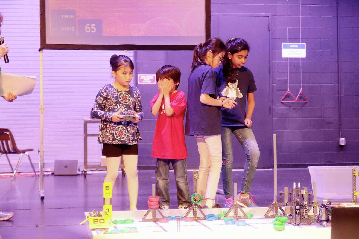 Vorarit Zhao can't look as Emma Morita guides a robot for Mandarin Immersion Magnet School while Kylee Leung and Ashita Virani of Galloway Private School in Friendswood focus on maneuvering their robot during the VEX Robotics Competition on Feb. 24 at Clear Brook High School.