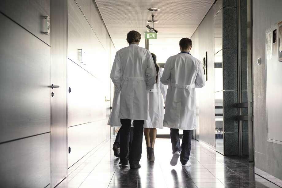 team of doctors walking in hospital hallway Photo: Buero Monaco/Getty Images
