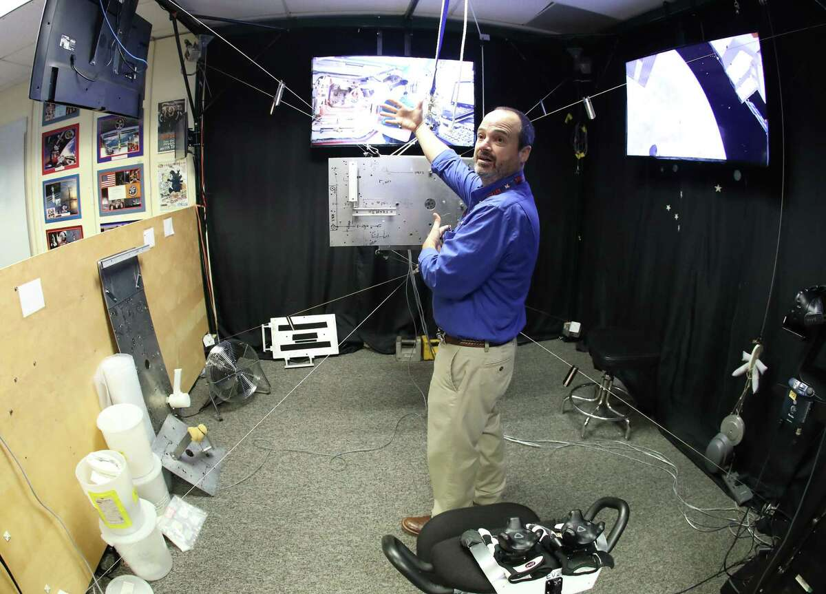 Eddie Paddock demonstrates Charlotte, which astronauts use as part of virtual reality at NASA Monday, Feb. 26, 2018, in Houston. Astronauts wear VR headsets and software turns Charlotte, a metal frame in the shape of a cube, into a piece of equipment to be installed on the outside the International Space Station.