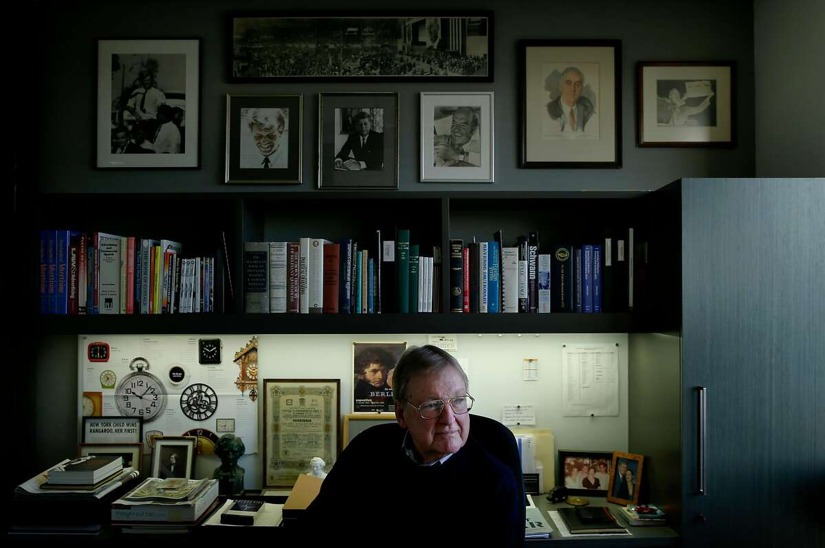John Anderson sits in his San Francisco office beneath photos of famous politicians, including Robert Kennedy, whose presidential campaign Anderson volunteered for as a young lawyer in 1968.