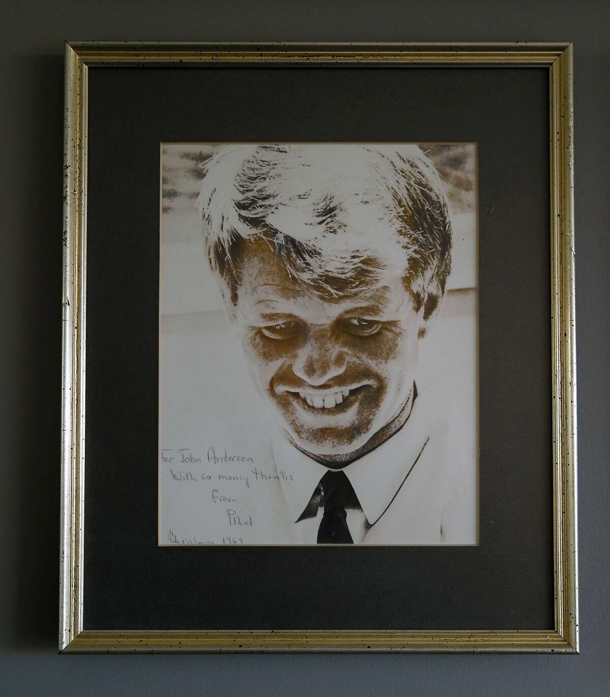 A framed photo of Robert F. Kennedy, signed and gifted by Ethel Kennedy, is seen on the wall of John Anderson's office.