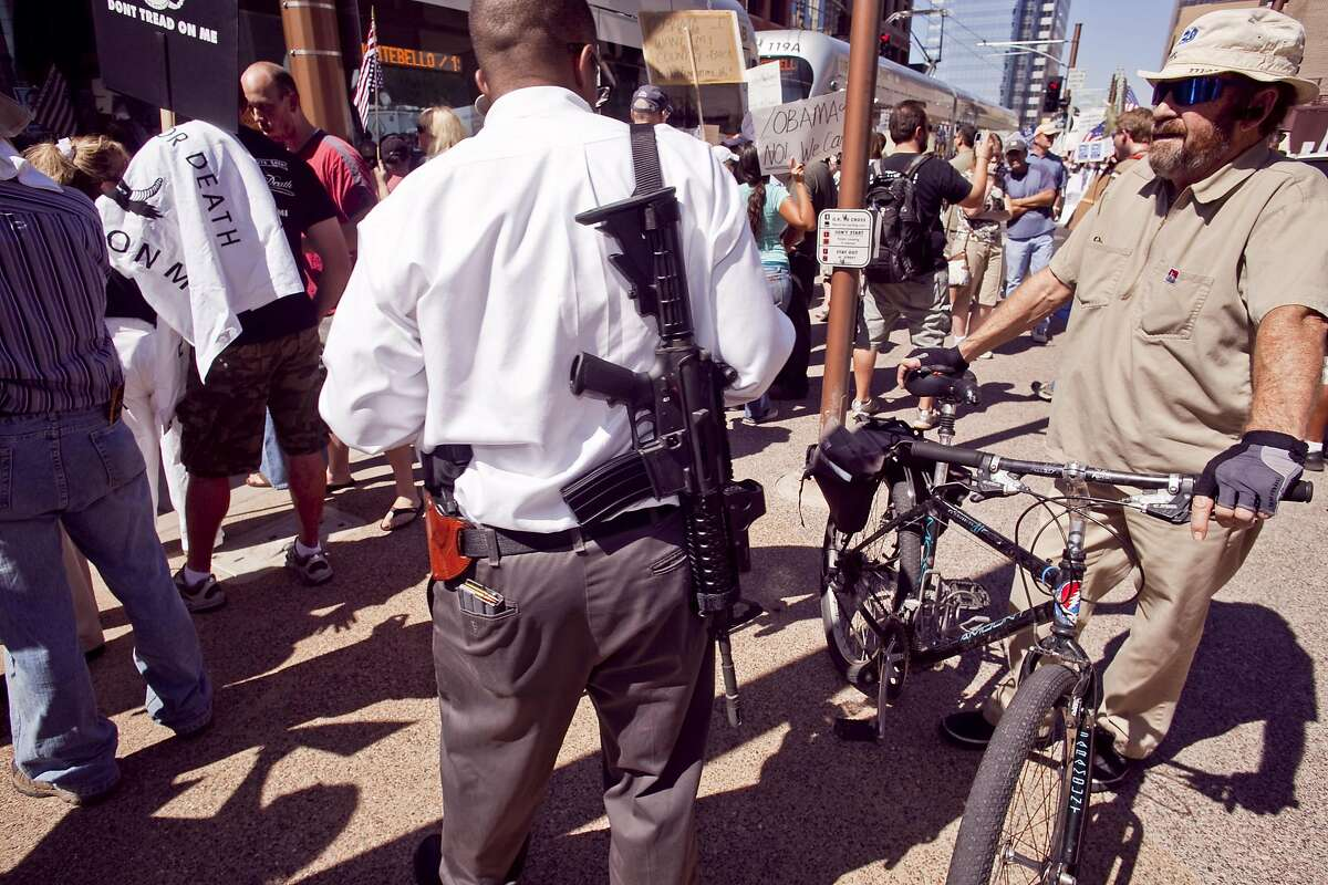 A man who supports the U.S. Constitution's Second Amendment right to keep and bear arms carries a military style AR-15 type rifle during a Obama opposition rally in Phoenix on Monday.