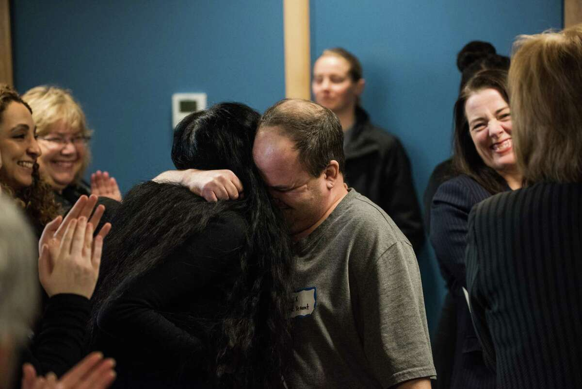 Alex Nichols receives hugs from the crowd after giving a moving testimony to the benefits of supportive housing during the opening ceremony of DESC's new supportive housing project, The Estelle, on Rainier Ave S, on Tuesday, Feb. 27, 2018.