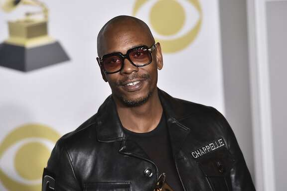 """FILE - In this Jan. 28, 2018 file photo, Dave Chappelle poses in the press room with the best comedy album award for """"The Age of Spin"""" and """"Deep in the Heart of Texas"""" at the 60th annual Grammy Awards at Madison Square Garden in New York.   Chappelle, Sandra Bullock, Christopher Walken, Rita Moreno and Helen Mirren are among the latest slate of stars set to appear on the 90th Academy Awards. Oscar telecast producers revealed another round of celebrity presenters on Tuesday, Feb. 17, 2018, which also includes Jane Fonda, Matthew McConaughey, Lupita Nyong�o, Nicole Kidman, Jodie Foster, Ashley Judd and Eugenio Derbez.(Photo by Charles Sykes/Invision/AP, File)"""
