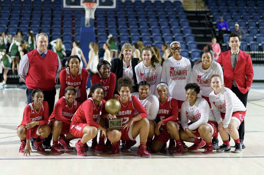 The Crosby Cougars girl's basketball team pose for a photo with their trophy after defeating the Cedar Park Timberwolves in a girls Region III 5A Semi-Final Championship basketball game on Friday, February 23, 2018 at Delmar Field House in Houston Texas. Photo: Wilf Thorne / © 2018 Houston Chronicle