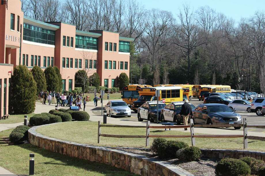 "Police, buses and students outside of Staples High School on Tuesday, after an ""unspecified threat"" led to a shelter-in-place command and early dismissal. Photo: Justin Papp / Hearst Connecticut Media / Westport News"