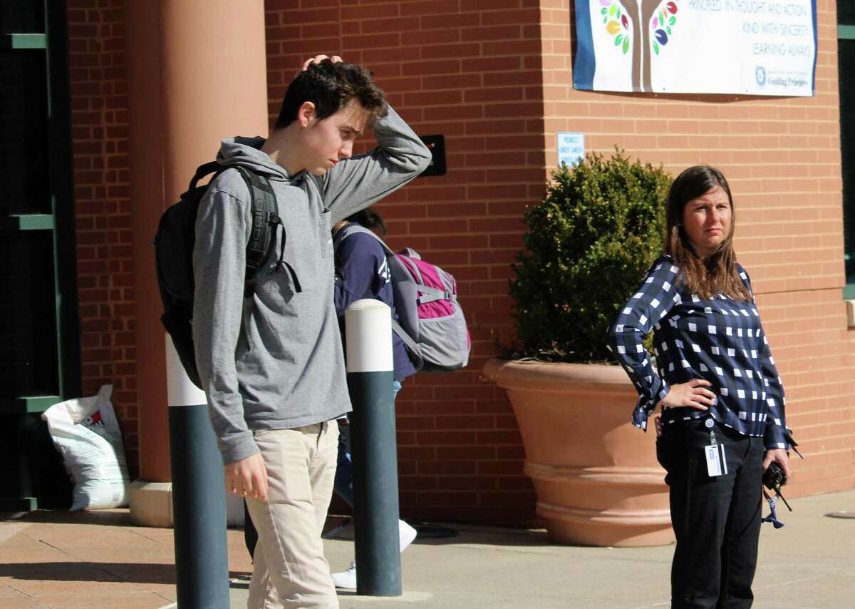 Staples High School junior Greg Settos waits to board a bus after the school was released early after being instructedto shelter in place by Superintendent of Schools Colleen Palmer on Tuesday, Feb. 27, 2018.