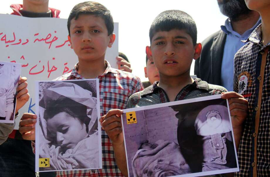 In this file photo taken on April 7, 2017 Syrian residents of Khan Sheikhun hold placards and pictures during a protest condemning a suspected chemical weapons attack on their town that killed at least 86 people. North Korea is suspected of sending Syria materials to make chemical weapons. Photo: OMAR HAJ KADOUR / Omar Haj Kadour / AFP/Getty Images / AFP or licensors